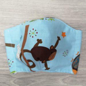 masque pour enfant avec motif de singe sur fond bleu, élastiques avec un nœud pour ajuster et espace pour filtre.